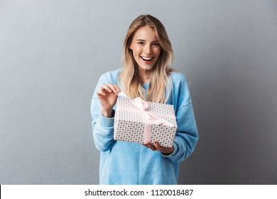 Portrait of a smiling young blonde girl unwrapping present box isolated over gray background