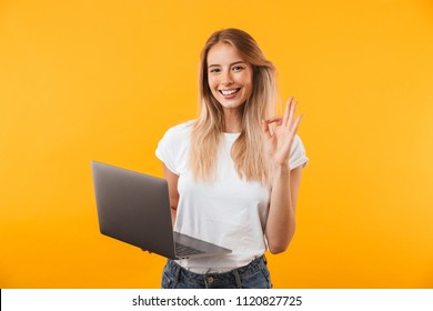 Portrait of a smiling young blonde girl holding laptop computer and showing ok gesture isolated over yellow background