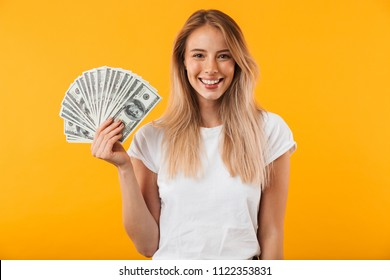 Portrait of a smiling young blonde girl showing bunch of money banknotes isolated over yellow background