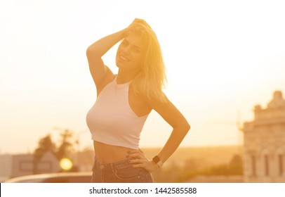 Portrait of a smiling young blonde girl standing outdoors during sunset.