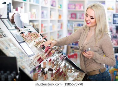 Portrait of smiling young blondie selecting lipstick in store