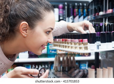 Portrait of smiling young brunette selecting lipstick in a cosmetics shop