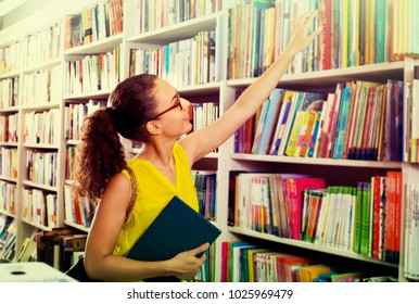 portrait of smiling young brunette woman picking books from shelves in book shop