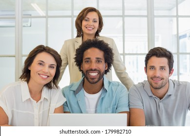 Portrait of smiling young business people using laptop together at office