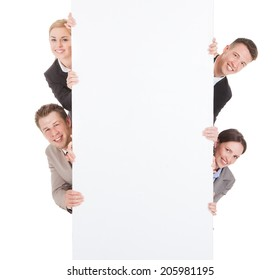 Portrait of smiling young business people looking from behind the blank billboard over white background