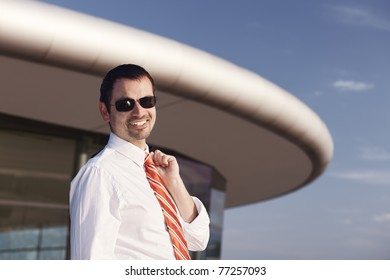 Portrait of smiling young business person in white shirt, orange tie and sunglasses standing in front of office building.