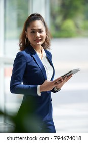 Portrait of smiling young business woman with digital tablet in her hands