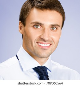 Portrait of smiling young businessman, against grey background