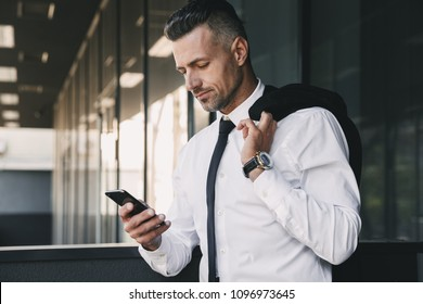 Portrait of a smiling young businessman dressed in formal clothes standing outside a glass building with jacket over his shoulder and using mobile phone