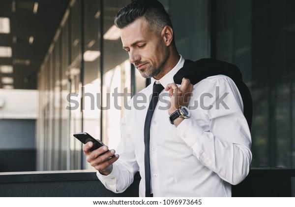 Портрет улыбающегося молодого бизнесмена, одетого в формальную одежду, стоящего за стеклянным зданием с курткой над плечом и с помощью мобильного телефона