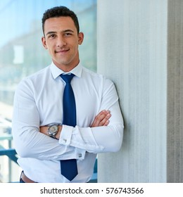 Portrait of a smiling young businessman in a shirt and tie standing with his arms crossed by windows high up in an office tower