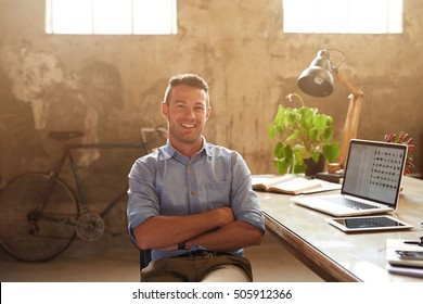 Portrait of a smiling young businessman sitting with his arms crossed at a desk in a trendy office