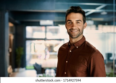Portrait of a smiling young businessman standing alone in a dark office while working late - Shutterstock ID 1714927594
