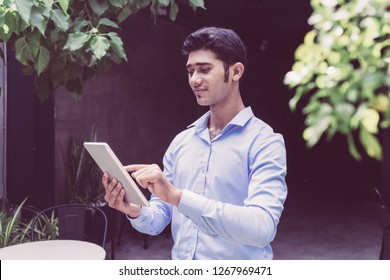 Portrait of smiling young businessman using digital tablet. Indian man networking on touchpad in sidewalk cafe. Modern technology concept