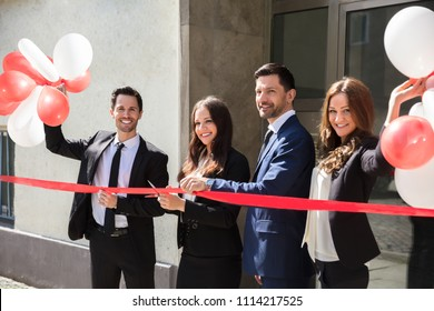 Portrait Of Smiling Young Businesspeople Cutting Red Ribbon