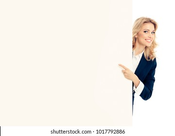 Portrait of smiling young businesswoman in blue suit, showing blank signboard with copyspace empty area for slogan or advertise text, isolated over white background. Advertising concept.
