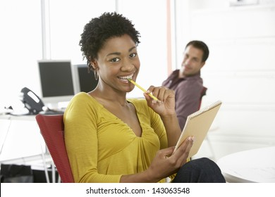 Portrait of smiling young businesswoman holding pencil and notepad with colleague in background