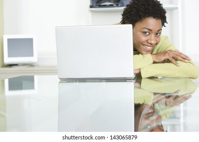 Portrait of smiling young businesswoman with laptop on table