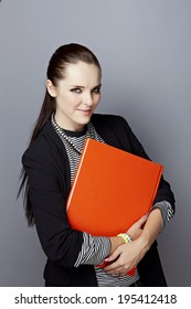 Portrait of a smiling young businesswoman, with long brunette hair, on gray studio background, holding a closed red book or album in her hands