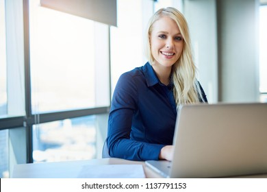 Portrait of a smiling young businesswoman sitting alone at a desk in a modern office working on a laptop