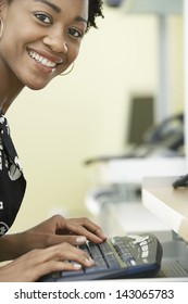 Portrait of smiling young businesswoman typing on computer keyboard in office