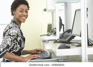 Portrait of smiling young businesswoman using computer in office