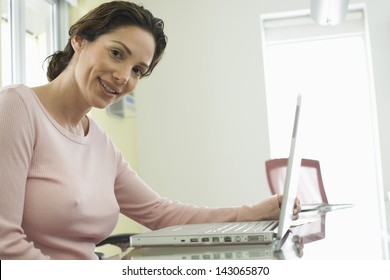 Portrait of smiling young businesswoman using laptop in conference room