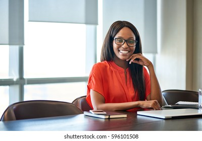 Portrait of a smiling young businesswoman wearing glasses sitting with her hand on her chin at a desk in a modern office