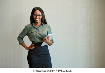 Portrait of a smiling young businesswoman wearing glasses and using a digital tablet while standing alone in a modern office