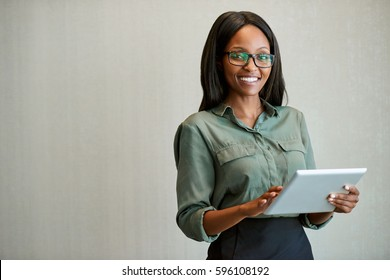 Portrait of a smiling young businesswoman wearing glasses and and using a digital tablet while standing alone in a modern office