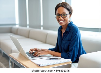 Portrait of a smiling young businesswoman wearing glasses working on a laptop while sitting at a table in a modern office