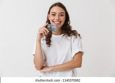 Portrait of a smiling young casual brunette woman holding credit card isolated over white background