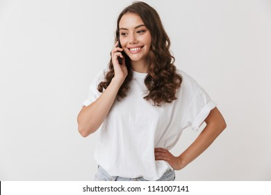 Portrait of a smiling young casual brunette woman talking on mobile phone isolated over white background