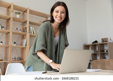 Portrait of smiling young Caucasian businesswoman work online on computer in modern office. Happy 30s female employee or worker use laptop, consult client or customer on web. Technology concept.