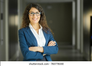 Portrait of smiling young Caucasian businesswoman wearing glasses in office