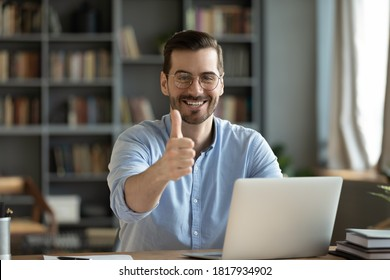 Portrait of smiling young Caucasian man in glasses sit at desk work on laptop recommend online course or training. Happy millennial male show thumb up give recommendation to distant education.