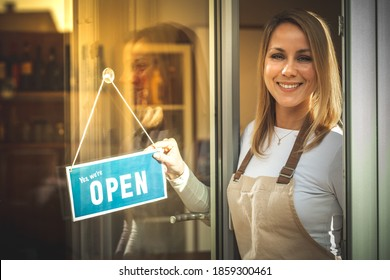 Portrait of a smiling young Caucasian woman with a beige apron puts a sign ''we are open'' and opening the coffee shop door