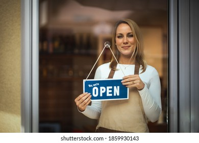 Portrait of a smiling young Caucasian woman with apron, puts a sign ''we are open'' on the door