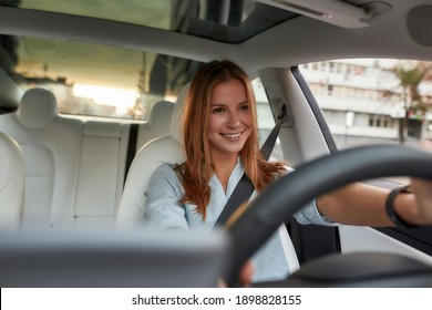 Portrait of smiling young caucasian woman sitting alone on driver seat with fasten belt while driving modern car. Lifestyle and success concept