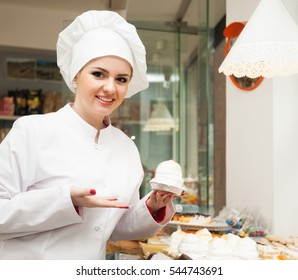 Portrait of smiling young chef with cook hat at confectionery display with pastry