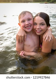 Portrait of smiling young children boy and girl giving a hug in the water outdoors.