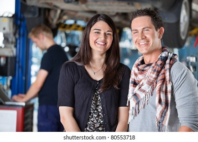 Portrait of smiling young couple in auto repair shop with mechanic in the background