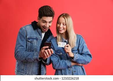 Portrait of a smiling young couple dressed in denim jackets standing together isolated over red background, using mobile phone, holding credit card