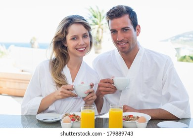 Portrait of a smiling young couple having breakfast at home