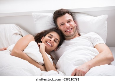 Portrait Of Smiling Young Couple Lying On Bed