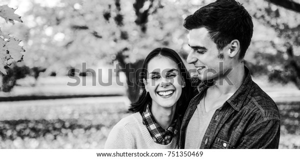 Portrait of smiling young couple outdoors in park in autumn