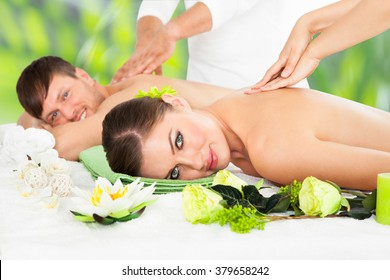 Portrait of smiling young couple receiving back massage at beauty spa