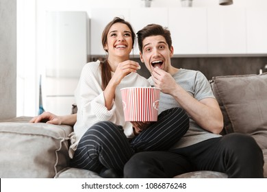 Portrait of a smiling young couple relaxing on a couch at home while watching TV and eating popcorn