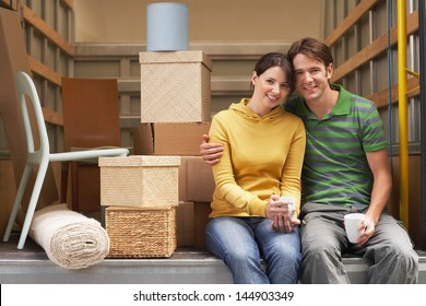 Portrait of smiling young couple sitting back of moving van