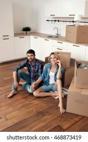 Portrait of smiling young couple sitting on wooden floor with unpacked boxes in new home